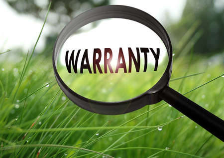 Magnifying glass with the word warranty on grass background. Selective focus Stock Photo