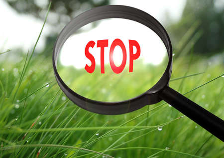 Magnifying glass with the word stop on grass background. Selective focus