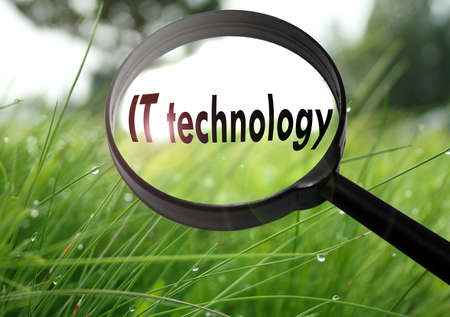 it technology: Magnifying glass with the word IT technology on grass background. Selective focus Stock Photo