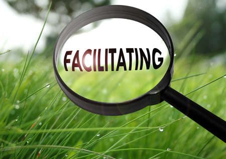 facilitating: Magnifying glass with the word facilitating on grass background. Selective focus Stock Photo