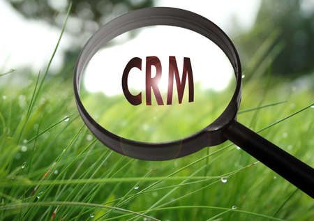 Magnifying glass with the word CRM (Customer Relationship Management) on grass background. Selective focus