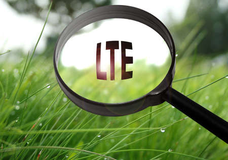 Magnifying glass with the word LTE (Long-Term Evolution) on grass background. Selective focus Stock Photo