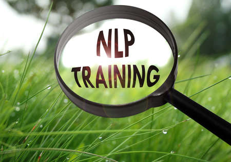 Magnifying glass with the word nlp training on grass background. Selective focus