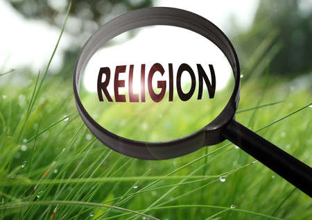 oneness: Magnifying glass with the word religion on grass background. Selective focus Stock Photo