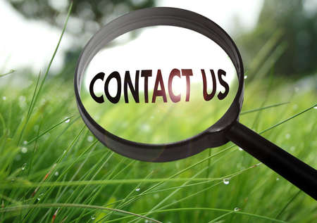 advise: Magnifying glass with the word contact us on grass background. Selective focus Stock Photo