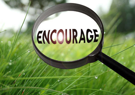 Magnifying glass with the word encourage on grass background. Selective focus