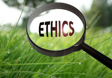 principles: Magnifying glass with the word ethics on grass background. Selective focus