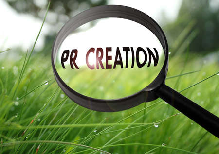 Magnifying glass with the word pr creation on grass background. Selective focus Imagens - 61940909