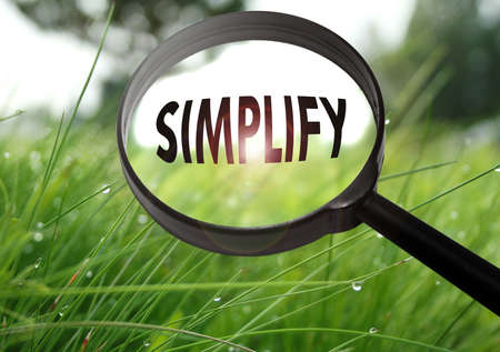 Magnifying glass with the word simplify on grass background. Selective focus