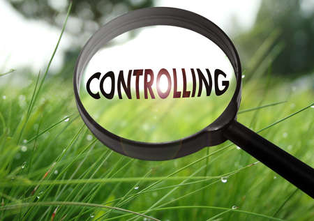 Magnifying glass with the word controlling on grass background. Selective focus