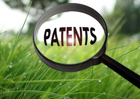 patents: Magnifying glass with the word patents on grass background. Selective focus