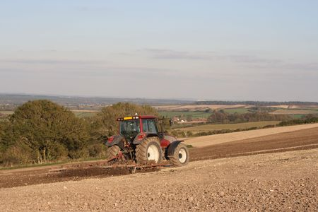 Tractor working on a field preparing the soil for planting. photo