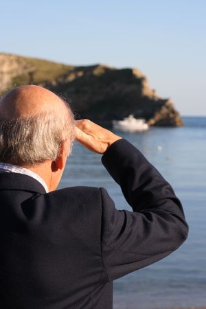 Senior retired man watching a small boat coming into harbour whilst shading his eyes or maybe a salute. Stock Photo - 2009743