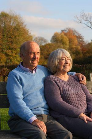 banc parc: Relaxed hauts couple sur un banc de parc  Banque d'images