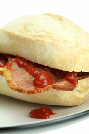 crust crusty: Bacon roll and tomato ketchup.