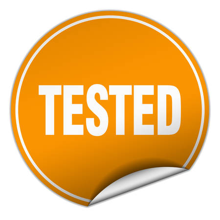 tested: tested round orange sticker isolated on white