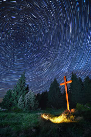 rotating star trails with illuminated wooden Christian cross 写真素材
