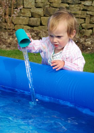 fascinate: Toddler pouring water into paddling pool.