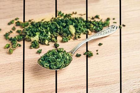 tannins: green tea in an iron spoon on wooden table