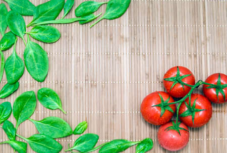 chinese spinach: green spinach leaves and branch of ripe tomatoes on a bamboo mat