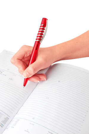hand with a red pen wrote in a diary Stock Photo - 11311338