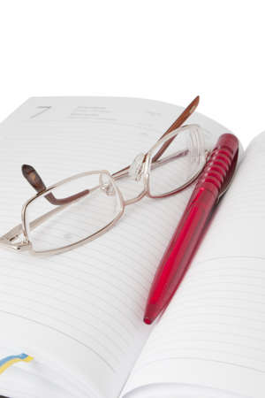 Reading glasses in an open diary with red pen close-up photo