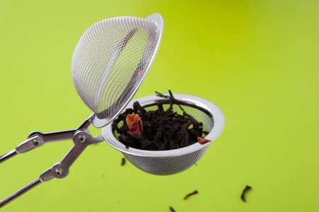 tea strainer: Tea infuser close-up of tea on a green background