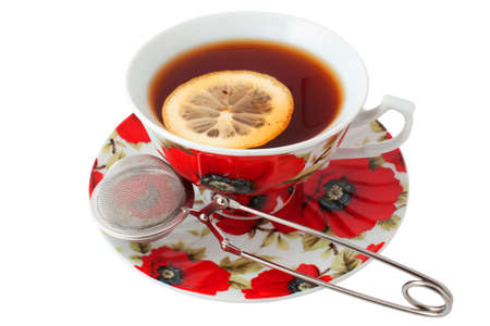 A cup of tea with lemon and tea infuser photo