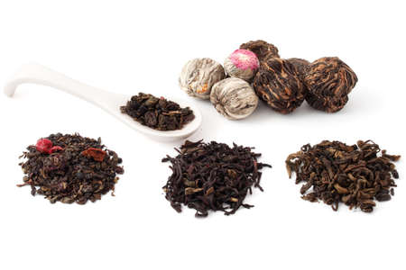 Dried leaves of different teas to zavrki and white spoon on white background photo
