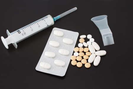 Spritze und Tabletten für die Inhalation Agent auf einem schwarzen Hintergrund