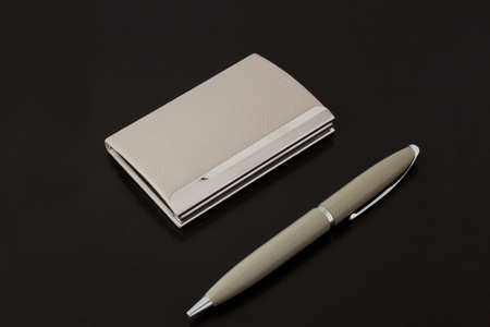 Card holder with pen gray on a black background