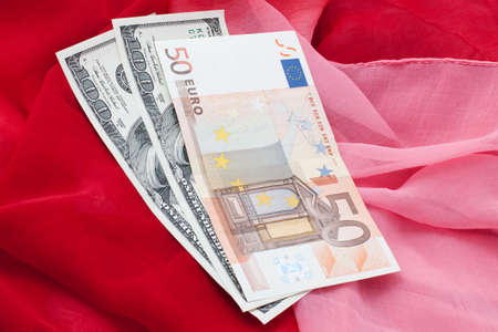 Money in dollars and euro on red fabric Stok Fotoğraf