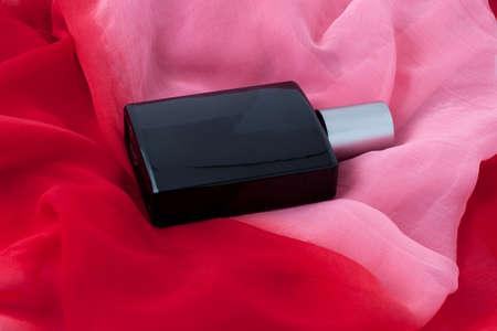 Parfüm von dunkler Farbe auf einem leuchtend roten Tuch