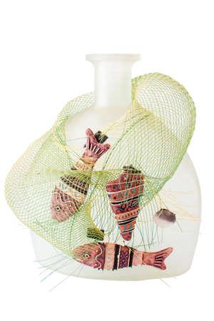 Dekorative Flasche mit Fisch und Tackle auf weißem Hintergrund