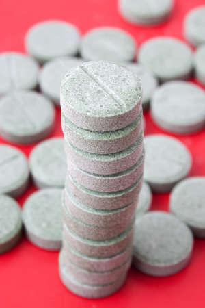 Tabletten voneinander auf einem roten Hintergrund zusammengesetzt Lizenzfreie Bilder