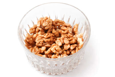 Walnuts in a glass on a white background