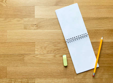Open blank notebook with pencil and eraser on wooden table.