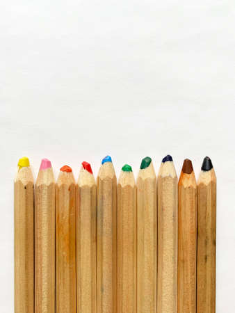 Old colored pencils row on white paper background. Zdjęcie Seryjne
