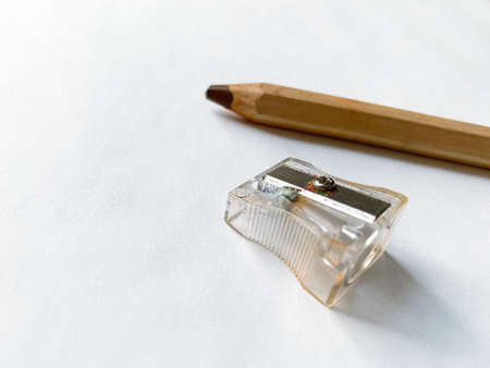Sharpener and brown pencil on white paper background. Selective focus on sharpener.