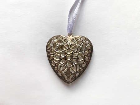 Metal heart pendant on a white paper background Zdjęcie Seryjne