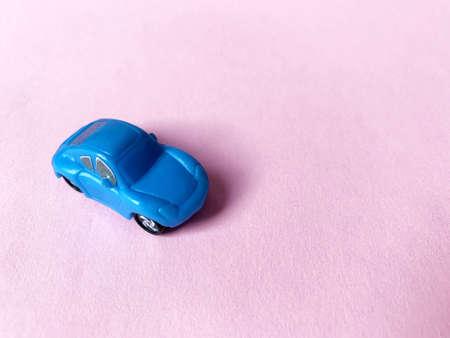 blue toy car on pink paper background Zdjęcie Seryjne
