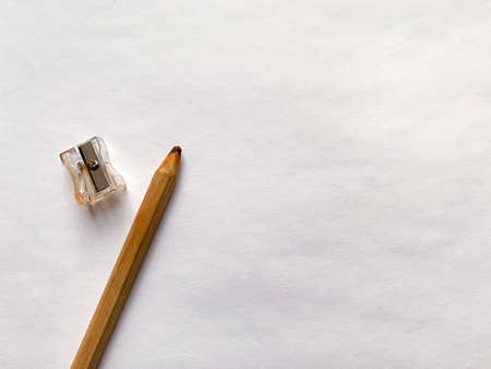 Sharpener and brown pencil on white paper background.