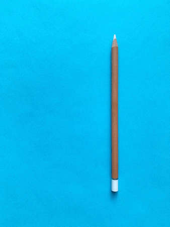 White wooden pencil on blue paper background.
