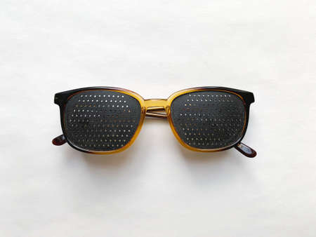 Special perforated glasses for vision correction on a white background. Zdjęcie Seryjne