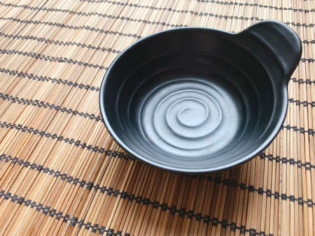 Black cup on wicker wooden napkin. Closeup.