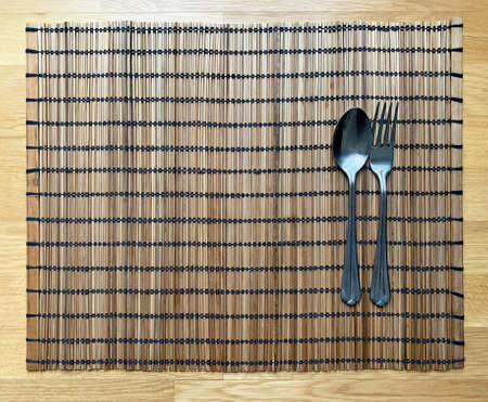 Wicker wooden napkin with spoon and fork. View from above Zdjęcie Seryjne