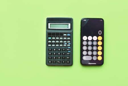 Digital calculator and calculator in smartphone on green background. technology development. Zdjęcie Seryjne