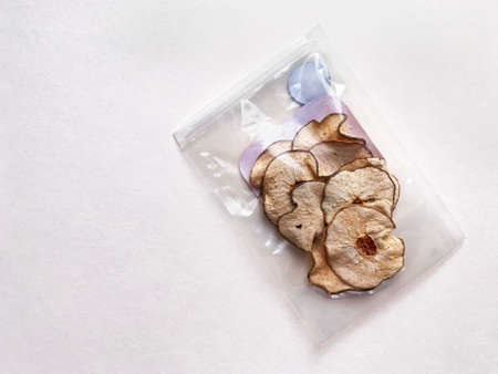 Pieces of dried pear in plastic packaging on white paper background. Zdjęcie Seryjne