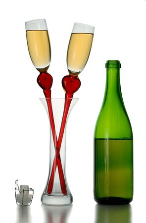 Pair of original wine glasses with champagne and bottle isolated on white background photo