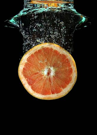 fishtank: Red grapefruit falling into water Stock Photo